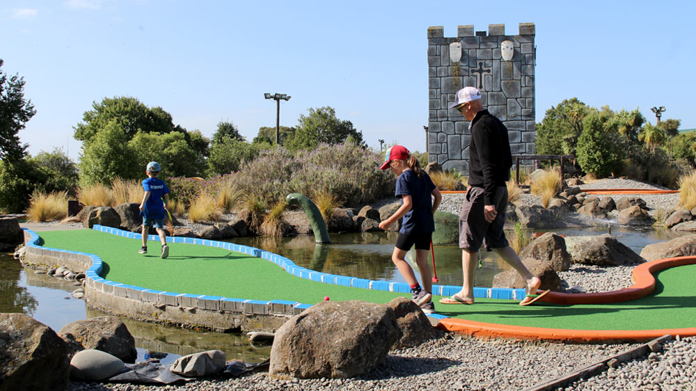 Dad and the Kids playing mini golf at Riccarton Golf Park during Christchurch School Holidays